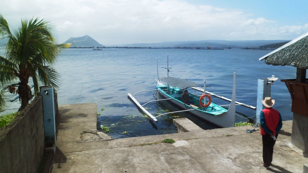 Show item 1 of 9. Outrigger canoe docked along the lakeshore in Manila