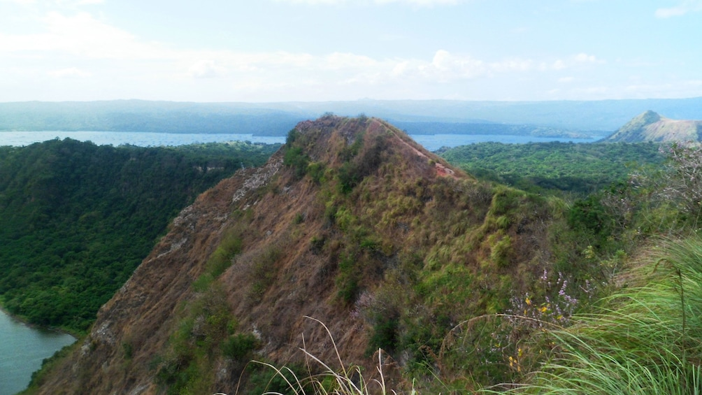 Show item 2 of 9. Tree covered cliffs along the edge of the Taal Volcano in Manila