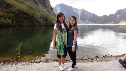 Pair of young women standing on the lakeshore with Mount Pinatubo in the background in the Philippines