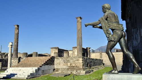 A bronze sculpture next to the ruins of the Temple of Apollo in Pompeii