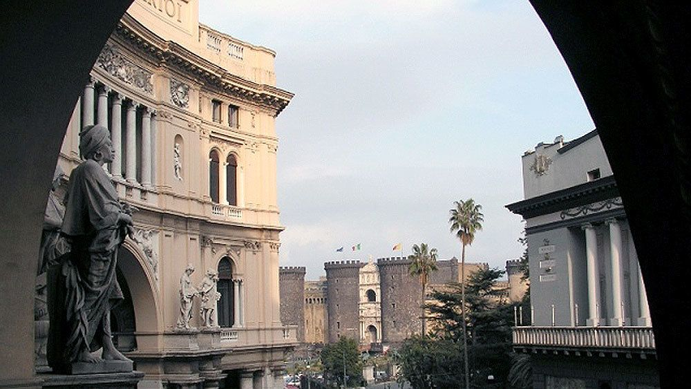 View through an archway at historic buildings and Castel Nuovo in the distance in Naples