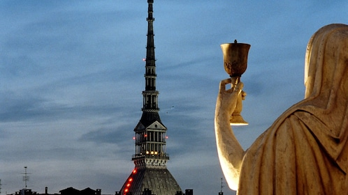 A statue of a female figure holding a cup looking out at a cathedral in Turin