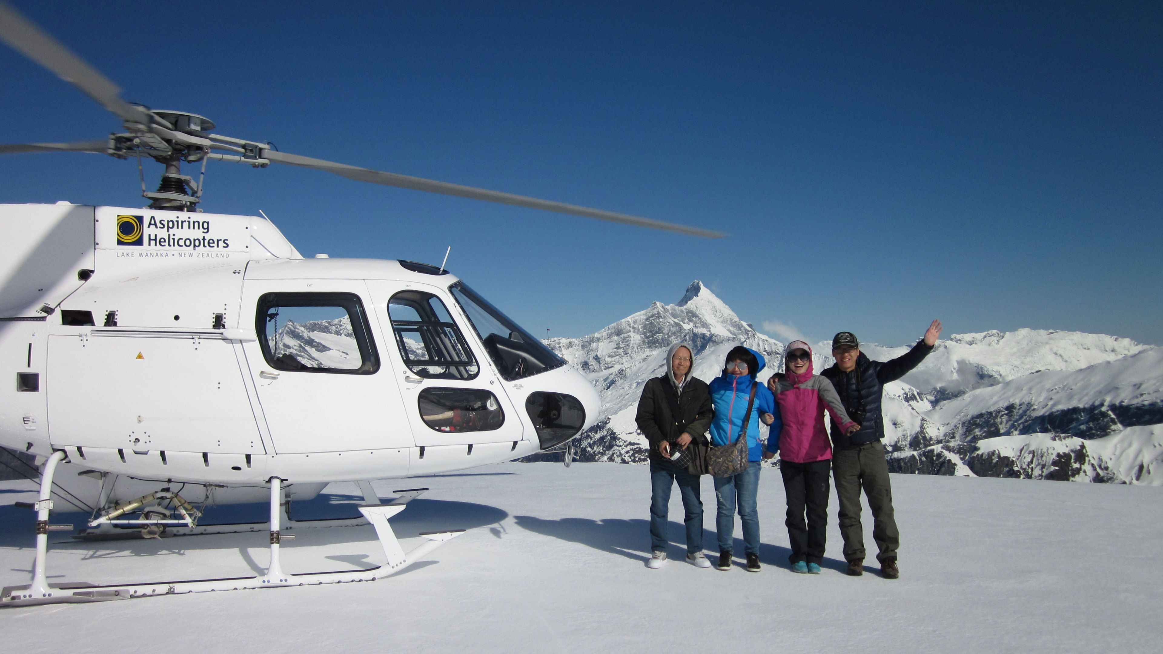 Group stands next to Helicopter on snowy mountain top