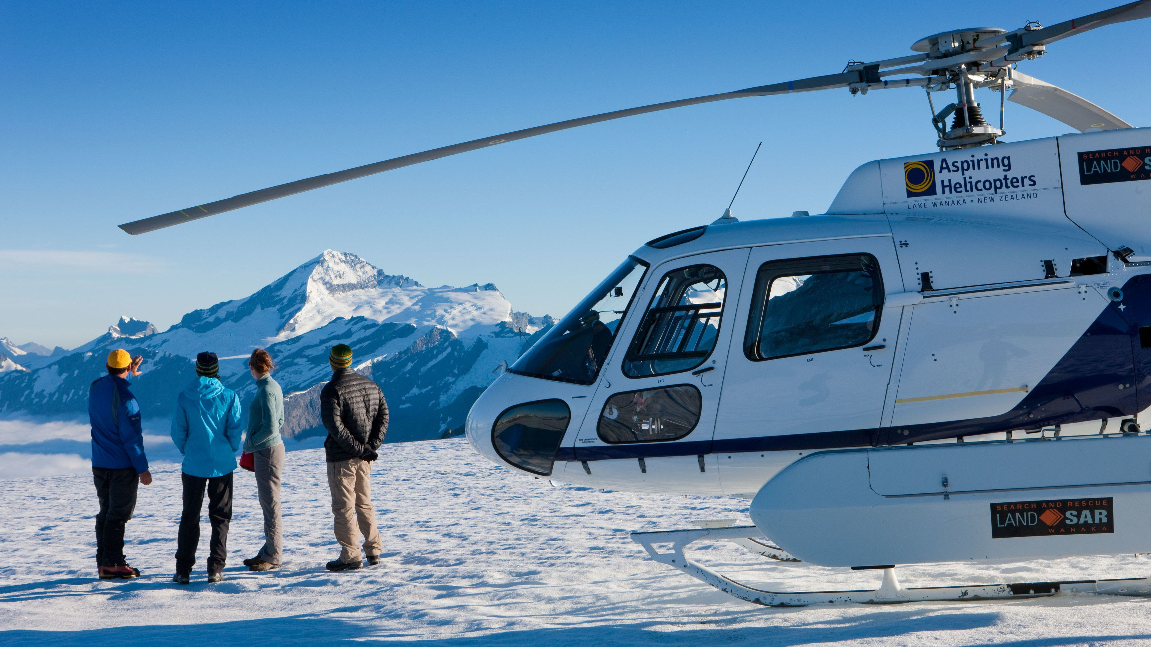 Tour group next to a Helicopter on a mountain top