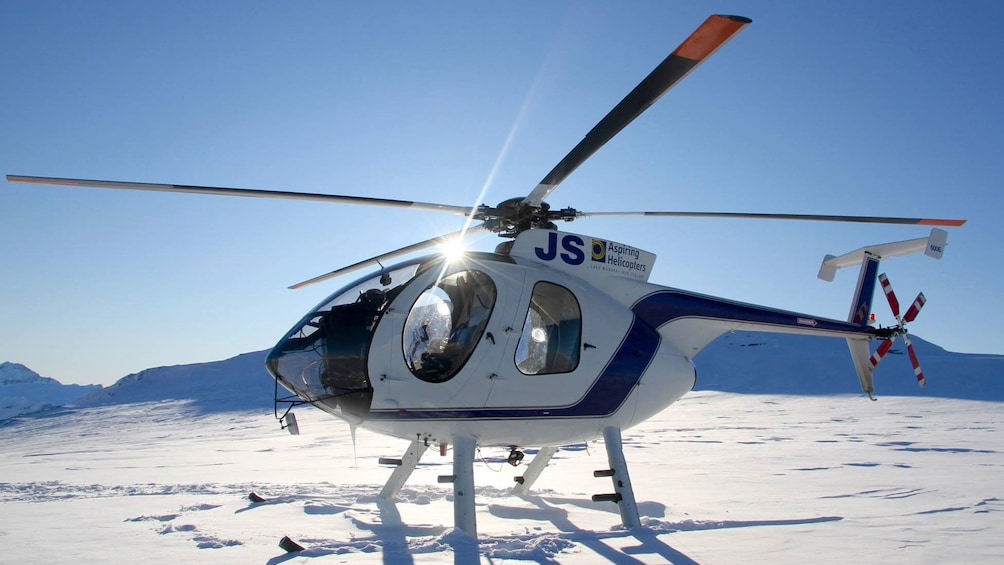 Show item 5 of 5. Helicopter on a snowy mountain top