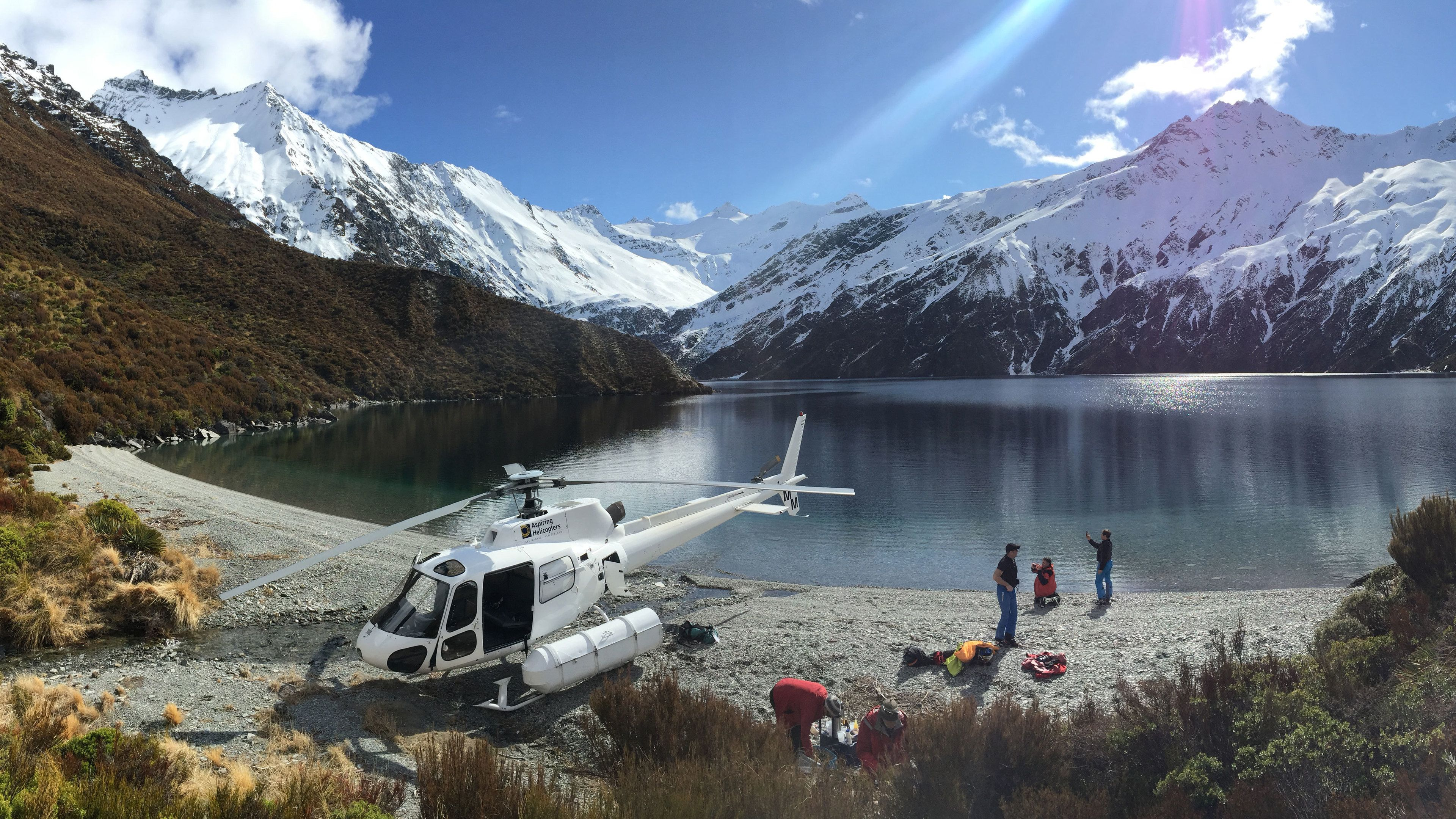 Helicopter next to a lake on a mountain top