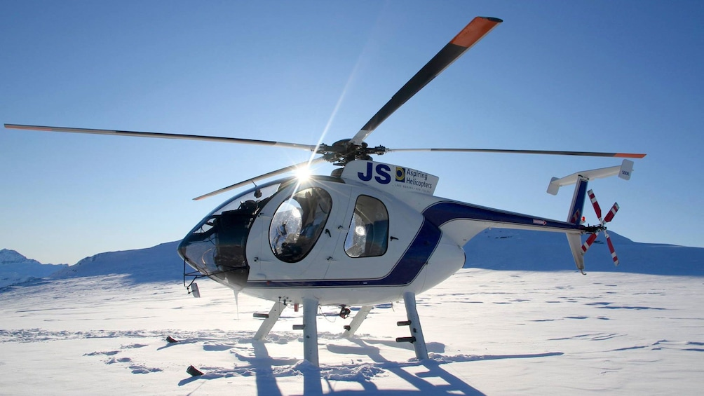 Show item 3 of 5. Helicopter on a snowy mountain top