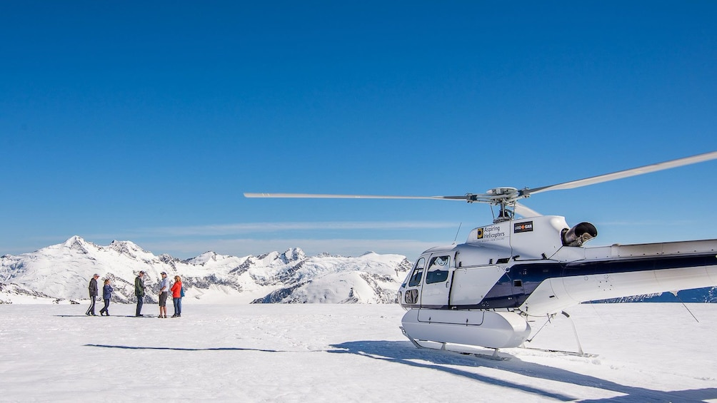 Show item 1 of 5. Tour group on a snowy mountain top next to Helicopter