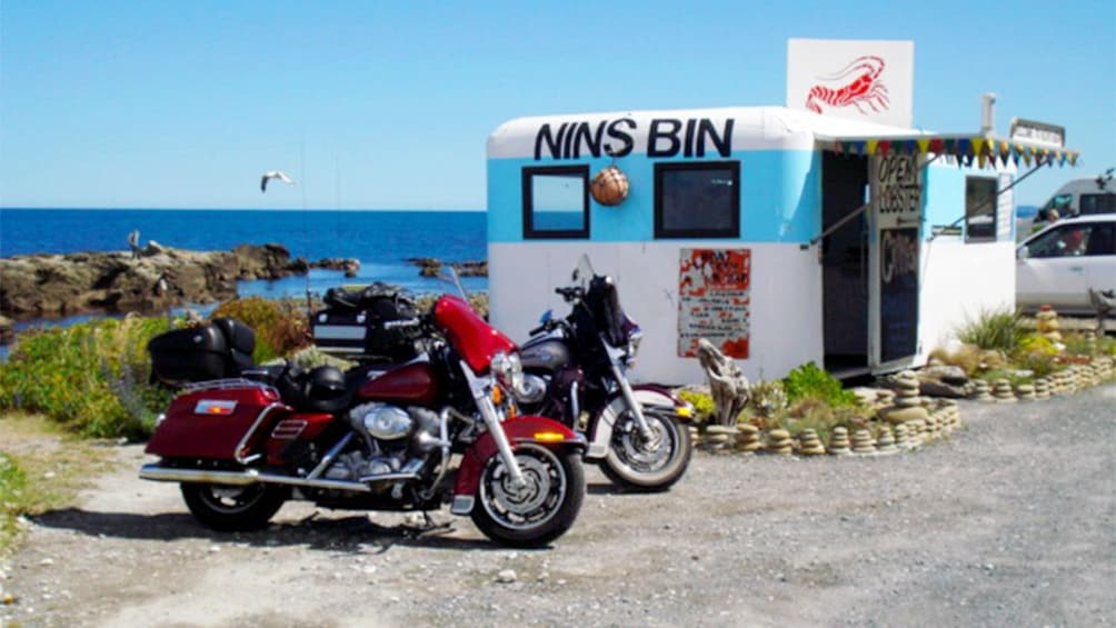 Show item 1 of 5. Motorcycles parked near roadside eatery in New Zealand