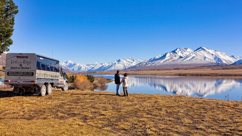 Show item 1 of 7. Couple looking at beautiful view of lake and mountains in New Zealand