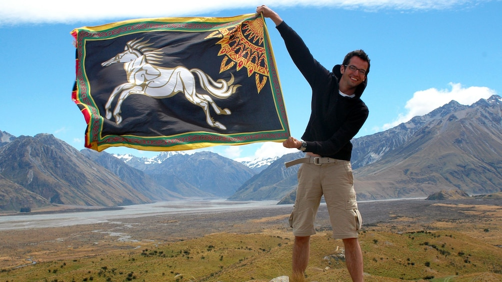 Show item 3 of 7. man holding flag in New zealand