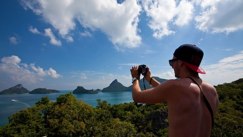 Man taking picture of mountains and water in Koh Samui