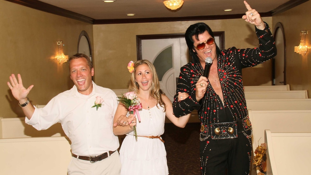 Show item 2 of 6. Happy bride and groom celebrating their marriage with Elvis presiding