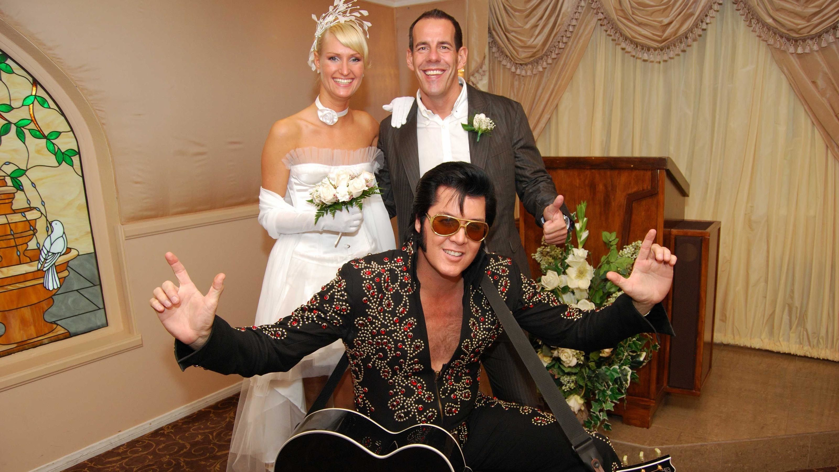 Beautiful bride and groom posing for a photo with Elvis at the wedding chapel
