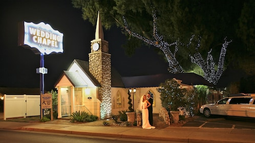 Evening photo with a happy bride and groom in front of the storybook wedding chapel