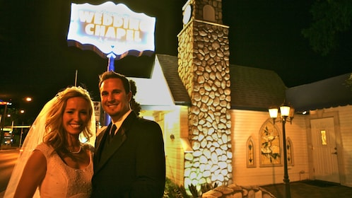 Happy bride and groom pose in front of the wedding chapel in celebration of their new marriage