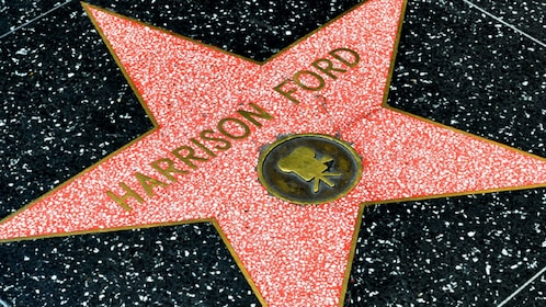 Walk down the Hollywood Walk of Fame to see star plaques of famous movie actors like Harrison Ford