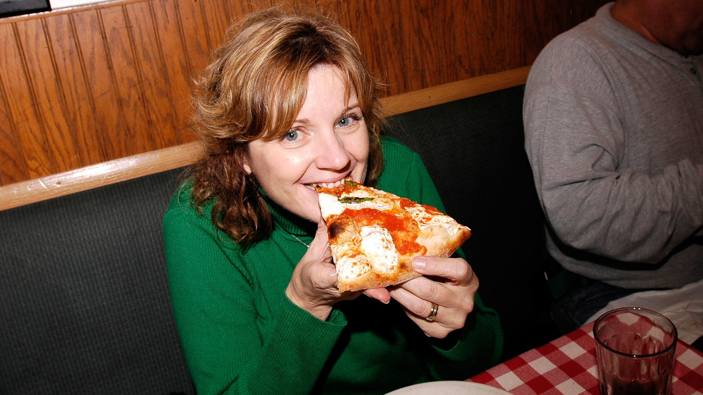Woman eating a slice of pizza in New York