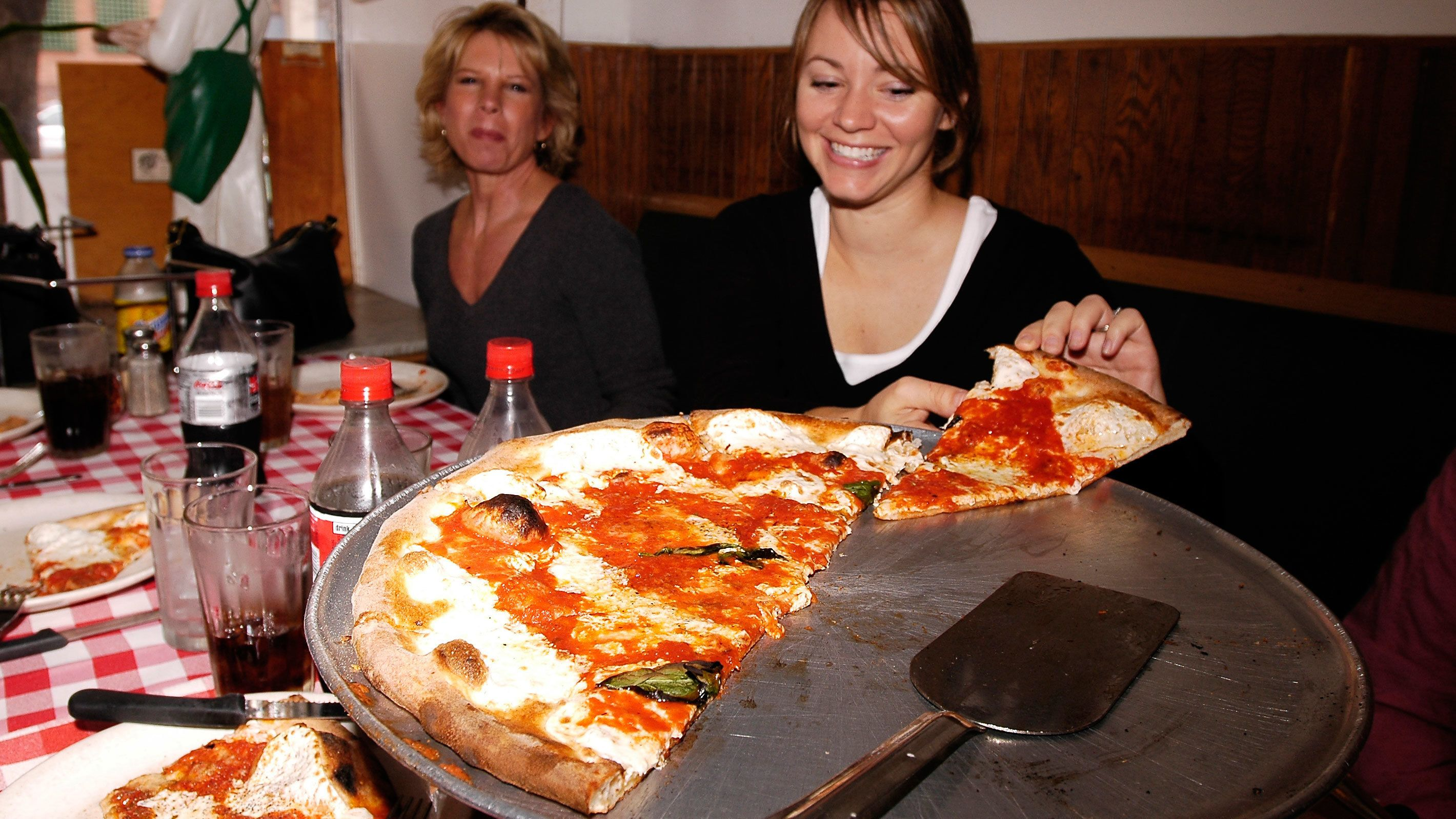Two women with pizza in New York