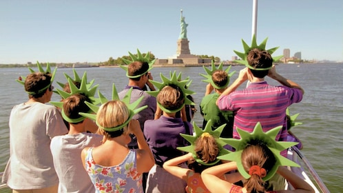 Tour group on a boat looking at the Statue of Liberty in New York