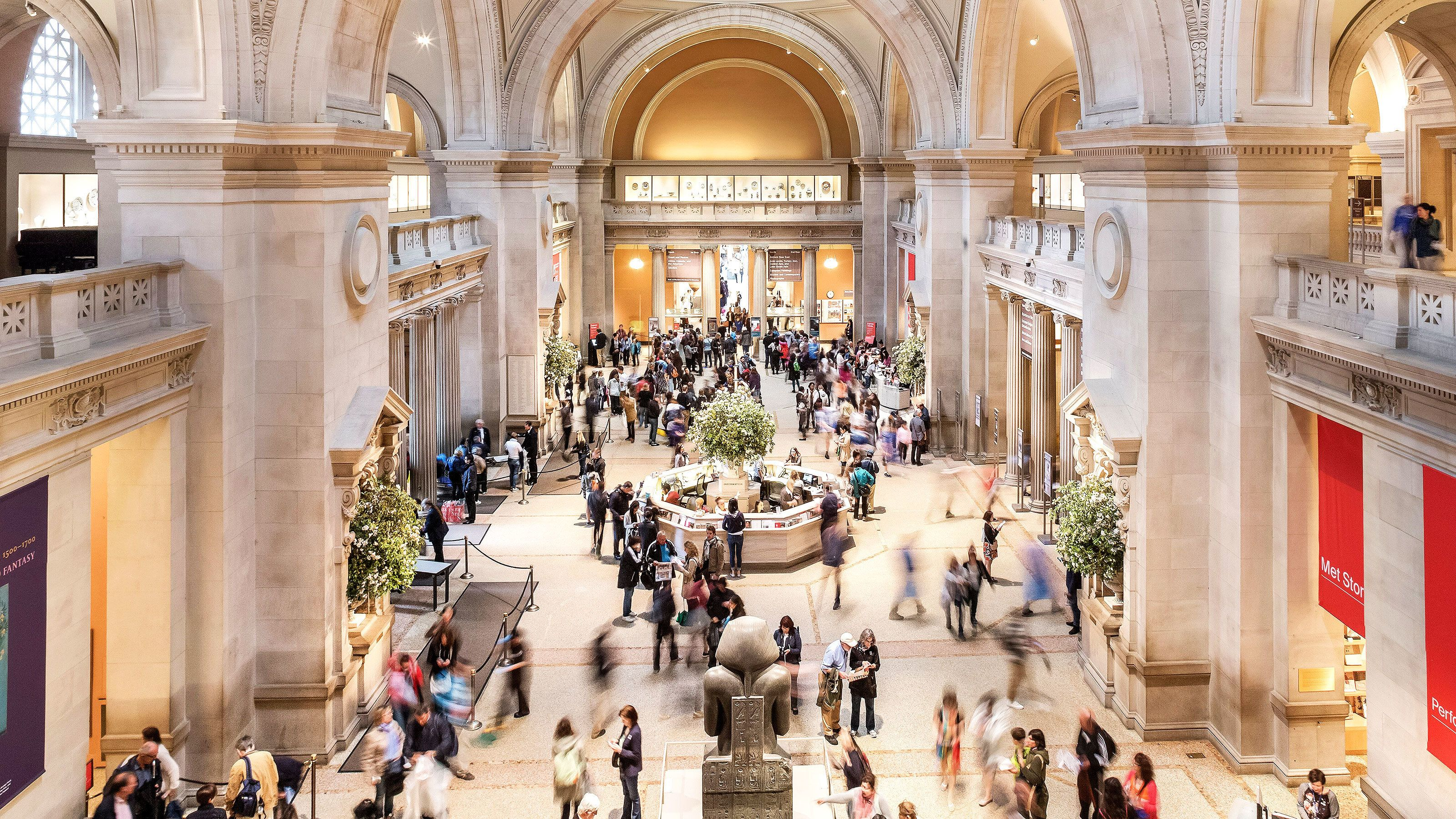 Tourist walking throughout the great hall in the Met in New York