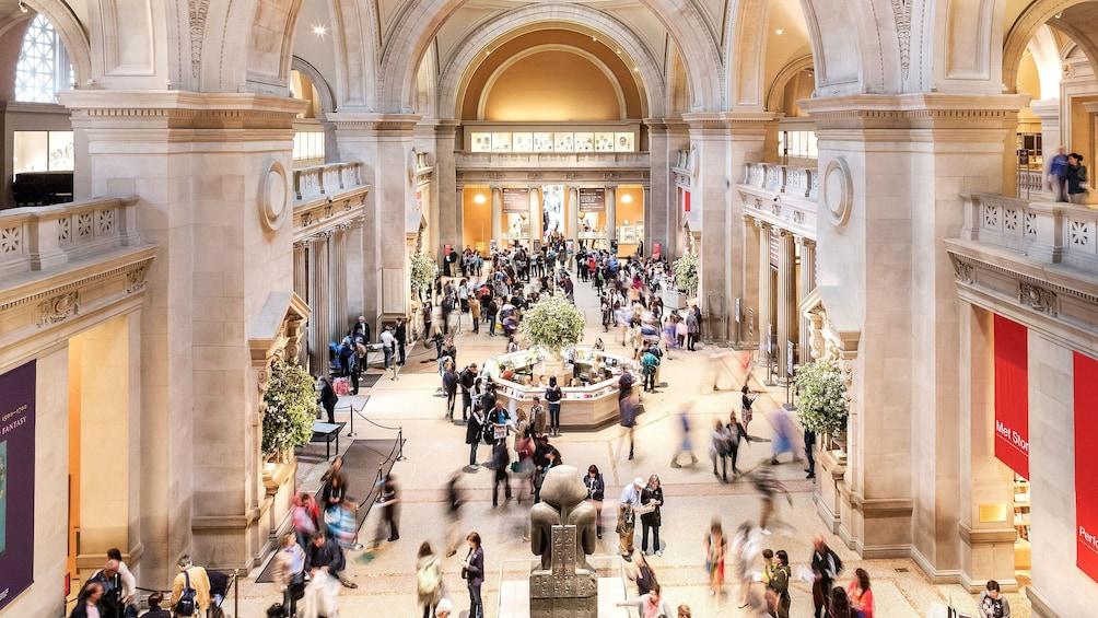 Foto 1 van 10. Tourist walking throughout the great hall in the Met in New York