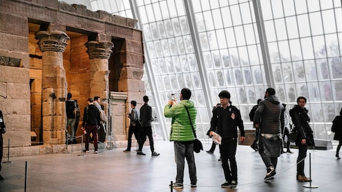 Tourists viewing the Temple of Dendur inside the Met in New York