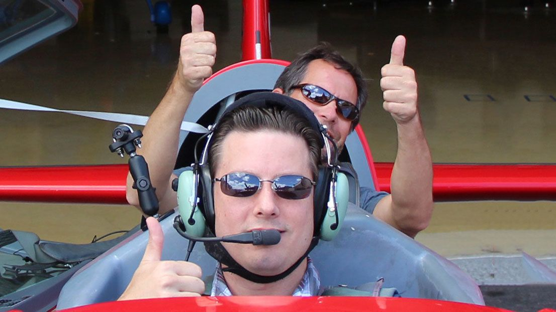 Two smiling men with thumbs up sign inside the airplane at Sky Combat Ace in Las Vegas