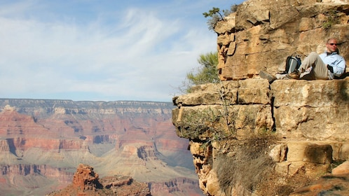 View of the Grand Canyon with a man resting on the canyon rock in Las Vegas