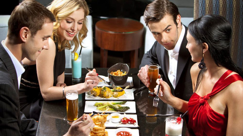 Two couples enjoying dinner at a dinner table in formal attire in Las Vegas