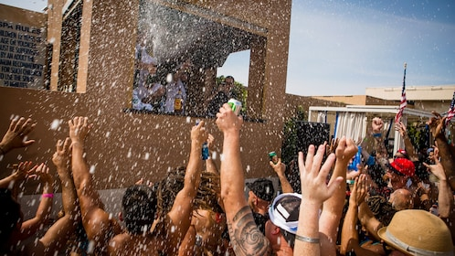 Guests at the Las Vegas pool party raising their hands and drinks in the air