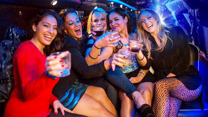 Group of young ladies holding up drinks and laughing inside a club in Las Vegas