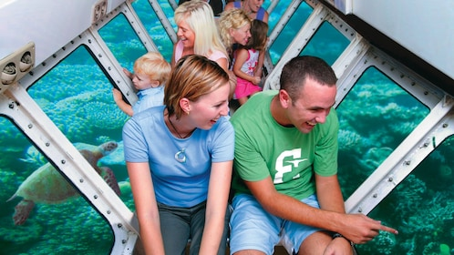 Tourists enjoying a glass-bottom boat view of the underwater world in Cairns