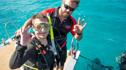 Deck hand and Snorkeler pose for photo at Stern of Catamaran