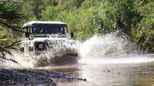Jeep splashing through the water in Algarve