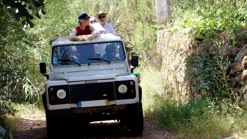 Show item 3 of 5. Jeep riding passengers stand and admire the lush green surroundings in the the Algarve