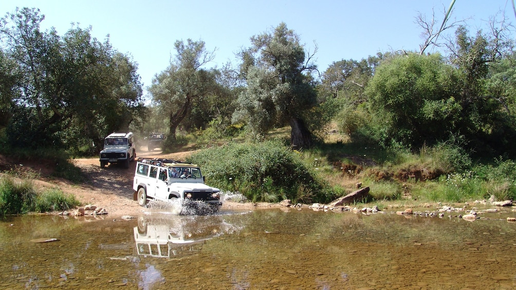 Show item 4 of 5. Row of jeeps splashing through water in the Algarve