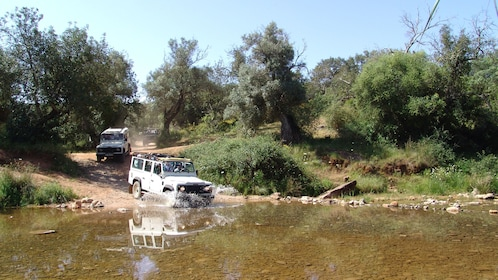 Row of jeeps splashing through water in the Algarve