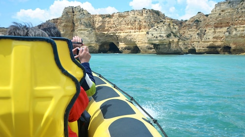 Tour boat passengers taking photos of the Insonia Caves in Algarve