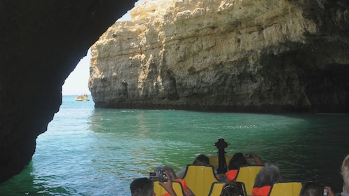 Boat traveling under the rock arches of the Insonia Caves in Algarve