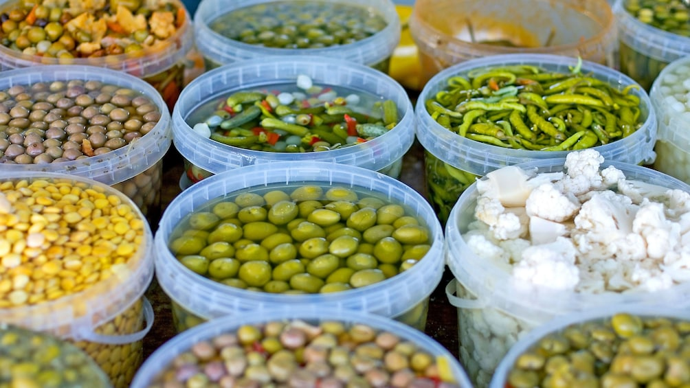 Show item 2 of 5. Bins of olives and marinated vegetables for sale at the Quarteira Market