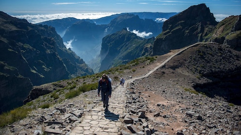 People walking up a path surrounded by scenic peaks in Madeira