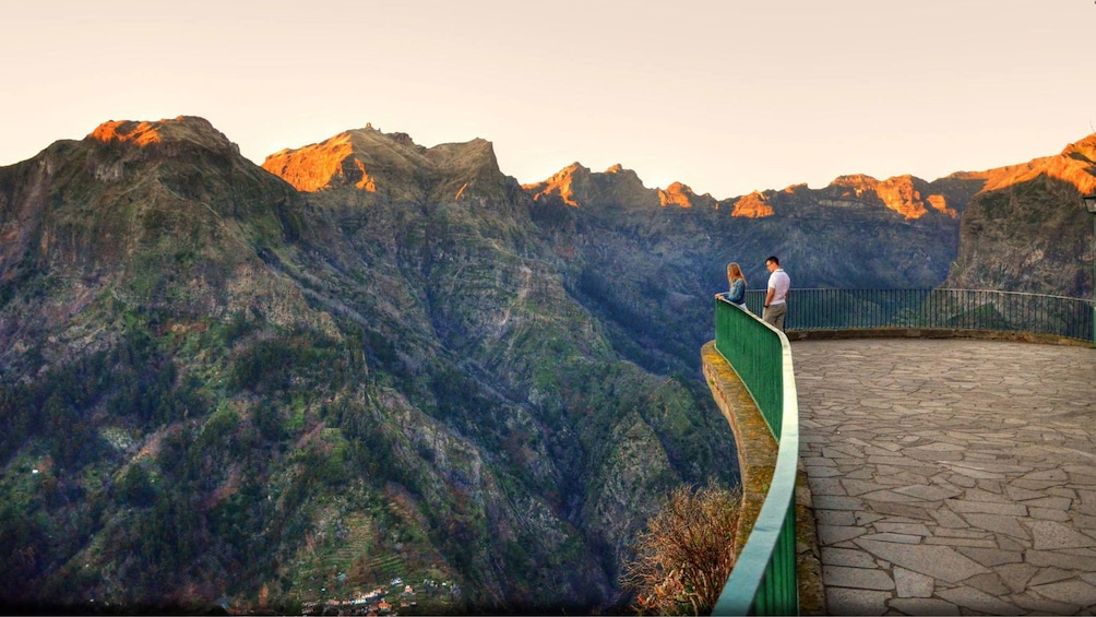 Two people at a vista point overlooking mountains in  Madeira