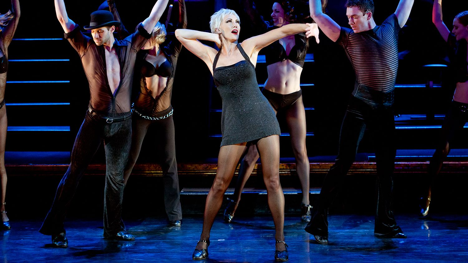 Actress playing Velma Kelley surrounded by dancers on stage in Chicago, the musical