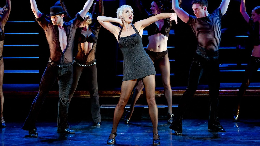 Show item 2 of 5. Actress playing Velma Kelley surrounded by dancers on stage in Chicago, the musical