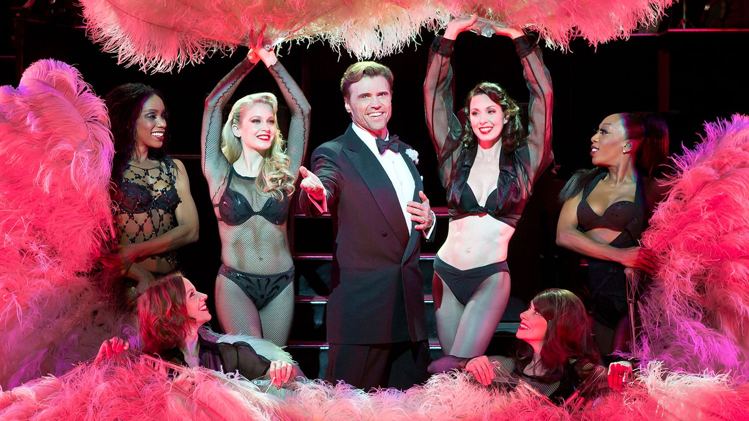 Man in tuxedo surrounded by women dancers in Chicago, the musical