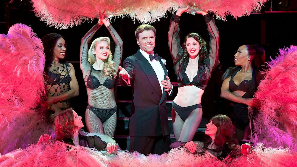 Show item 3 of 5. Man in tuxedo surrounded by women dancers in Chicago, the musical