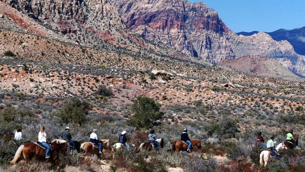 Show item 5 of 5. Landscape view of horseback riders venturing into the back country of the Wild West in Las Vegas