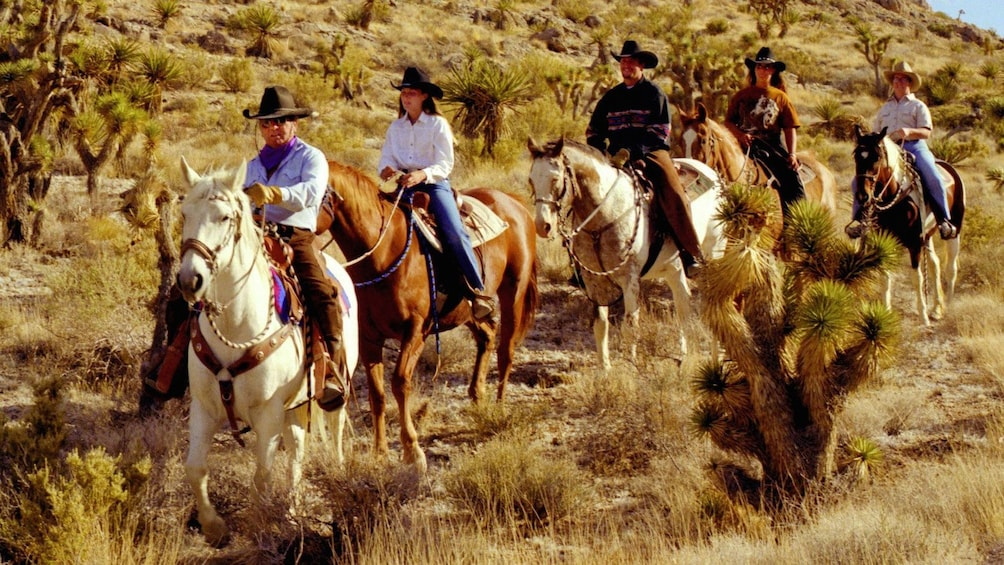 Show item 1 of 5. Horseback riders on a Wild West Horseback Riding tour in Las Vegas