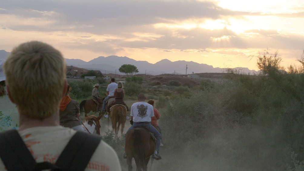 Show item 3 of 5. Group of horseback riders going into the Wild West in Las Vegas